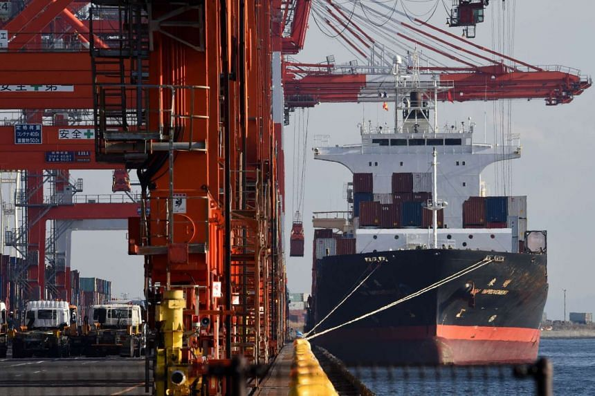 A container is loaded on a cargo ship at a pier in Tokyo.
