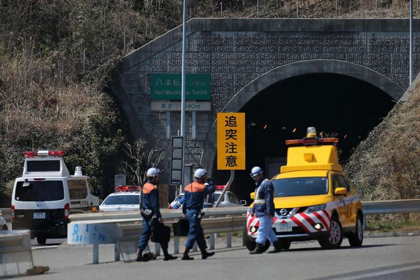 Policemen  gather at the entrance of the Hachihonmatsu tunnel in Hiroshima.