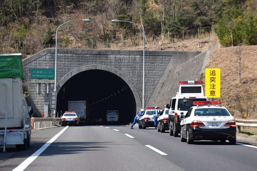 Police vehicles gather at the entrance of the Hachihonmatsu tunnel in Hiroshima.