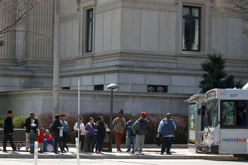 People stand at a bus stop on Pennsylvania Ave, Washington, after Metrorail shut down service entirely for emergency inspections.