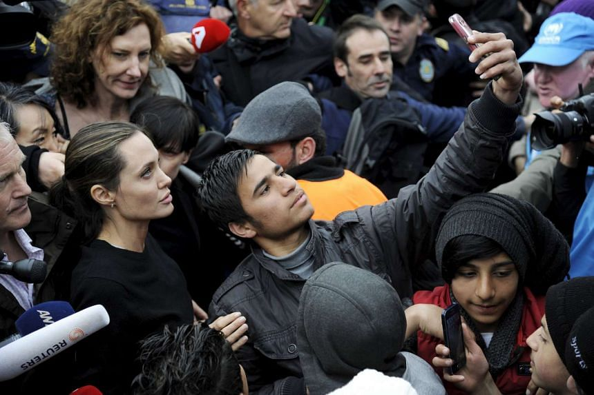 A refugee takes a selfie with Jolie in Greece.