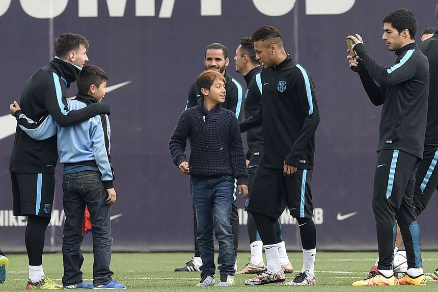 Barcelona's superstar attacking trio of Argentinian Lionel Messi (left), Brazilian Neymar (centre) and Uruguayan Luis Suarez taking pictures with children who gate-crashed a training session in Spain. The Spanish Primera Liga did not market itself strongl