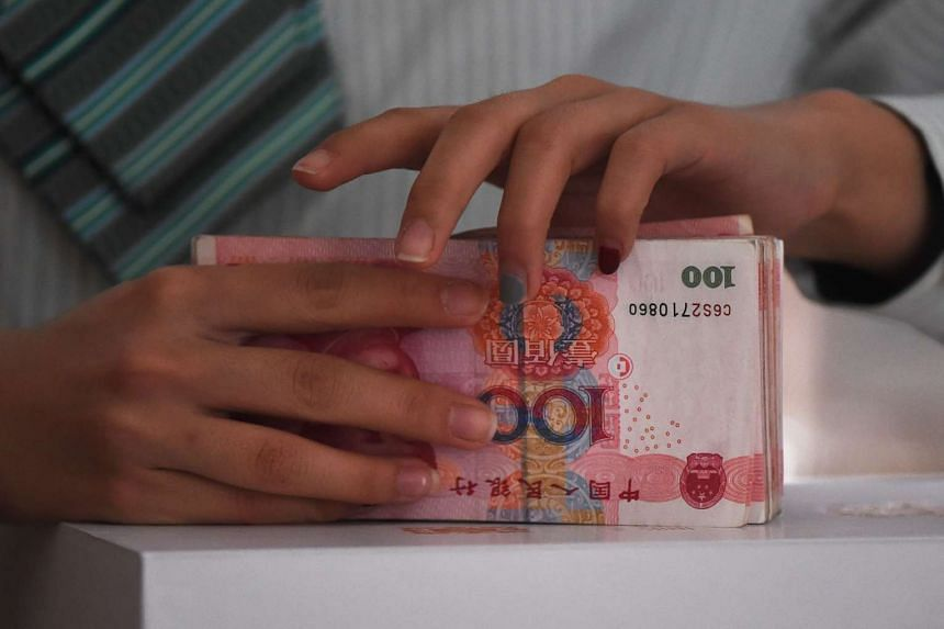 A post office employee counts Chinese yuan at a post office branch set up inside Beijing's Great Hall of the People.