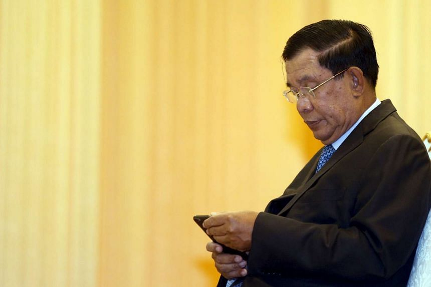 Cambodia's Prime Minister Hun Sen looks at his smartphone at a ceremony in Phnom Penh on Feb 25, 2016.