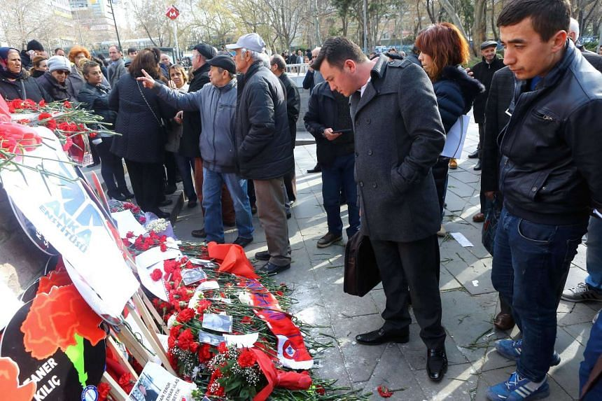 People look at flowers and photos displayed in remembrance of the victims of the attack in Ankara on March 17, 2016, on the site of the blast that killed 37 people on Sunday (March 13).