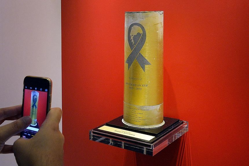 Left: The artillery shell casings from the 21-gun salute at Mr Lee's funeral on March 29 last year. Above: PA, one of the recipients, placed its gift near the entrance of its headquarters yesterday.
