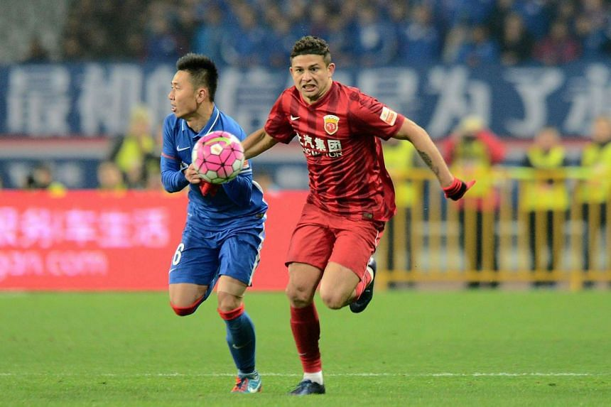 Elkeson De Oliveira Cardoso (right) of Shanghai SIPG competes for the ball with Li Yunqiu of Shanghai Shenhua during their Chinese Super League match on March 11, 2016.
