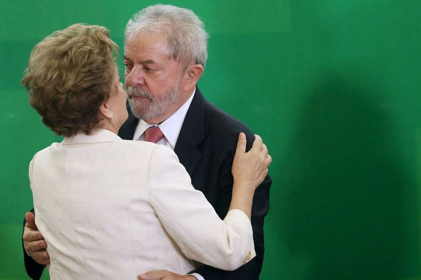 Rousseff (left) greets former president Luiz Inacio Lula da Silva during his appointment as chief of staff.