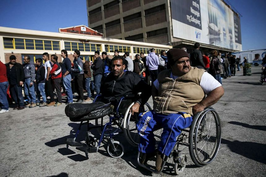 Mr Sheikho (left) and Mr Omar waiting for food outside a passenger terminal used as shelter at the port of Piraeus, Greece, on March 2.