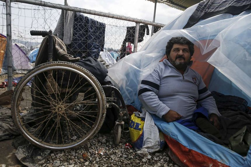 Mr Hassan Omar, 48, inside his tent next to his deflated wheelchair at a makeshift camp near the village of Idomeni, Greece, on March 17.