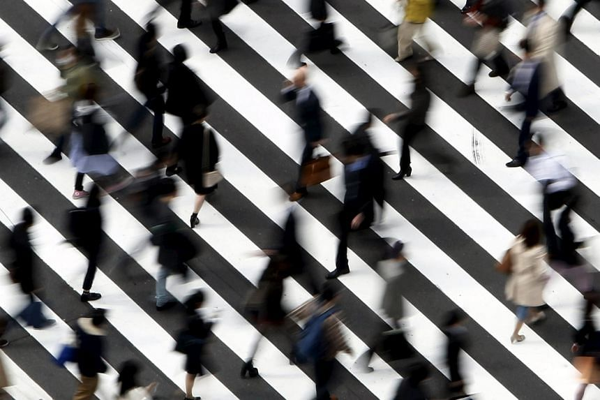 People cross a street in Tokyo, in this March 18, 2015 file photo.