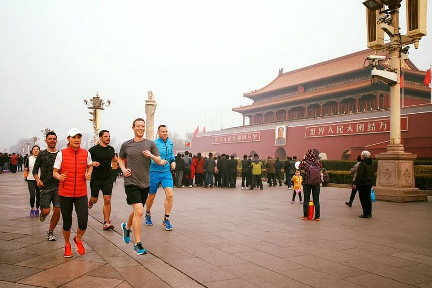 Mark Zuckerberg (in grey) taking a mask-free jog through Beijing's Tiananmen Square on March 18, 2016.