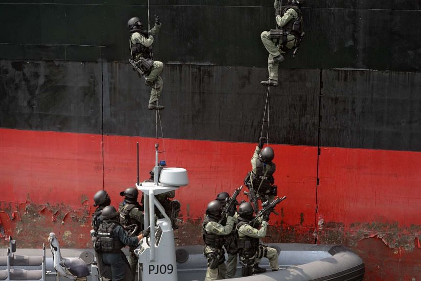 Members of the Singapore Police Force Special Tactics and Rescue Unit (STAR), supported by the Police Coast Guard (PCG) Special Task Squadron, storm a vessel during a showcase of their counter-terrorism and maritime security measures at PCG Brani Bas