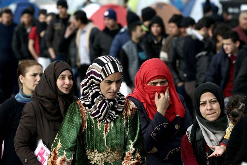 Women wait for food being distributed at Piraeus port near Athens on March 18, 2016.