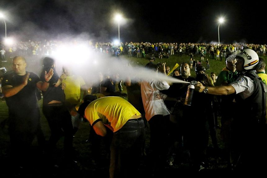 A police officer uses pepper spray against protesters in front of the Brazilian national congress on March 17.