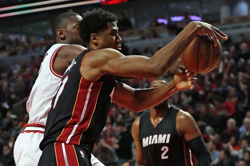 Hassan Whiteside (centre) of the Miami Heats grabs a rebound next to Bobby Portis of the Chicago Bulls.