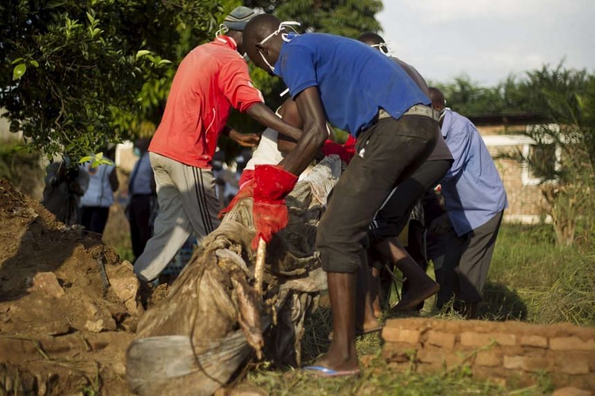 Volunteers recover body parts of an unknown person killed by suspected members of an armed group and buried in a mass grave in Mutakura, north of Burundi's capital Bujumbura, on Feb 29, 2016.