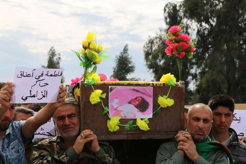 Iraqi Sameer Wais (right) carries the coffin of his three-year-old daughter, Fatima, who was killed following a chemical attack by the Islamic State of Iraq and Syria group against the town of Taza, south of Kirkuk, during her funeral on March 11, 20