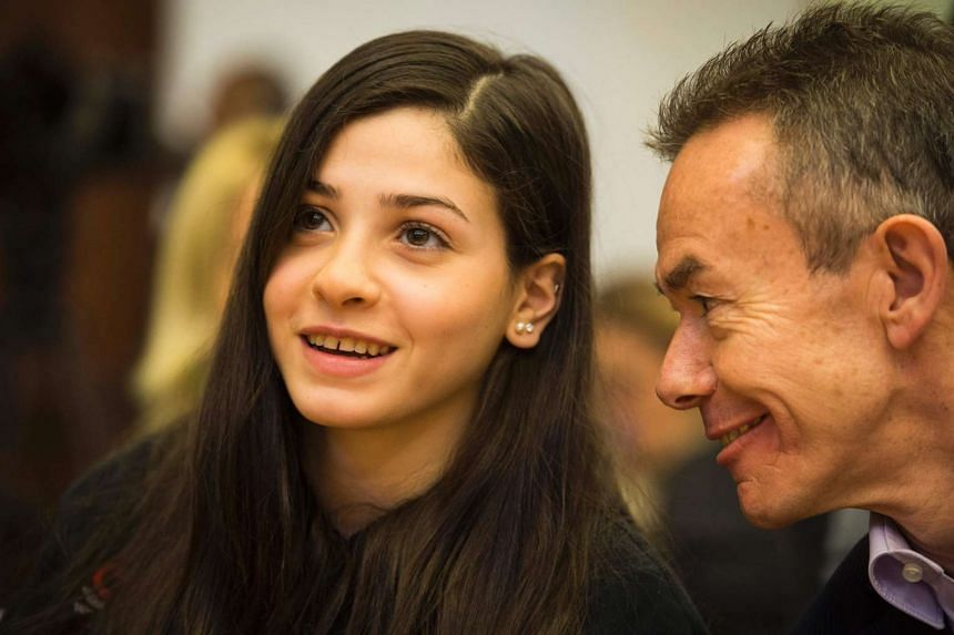 Syrian swimmer Yusra Mardini (left) and Pere Miro of the International Olympic committee (IOC) speak during a press conference in Berlin on March 18, 2016.