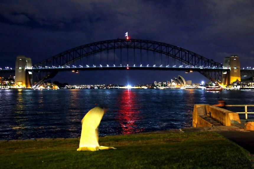 A woman in front of the Sydney Opera House and Harbour Bridge during Earth Hour.