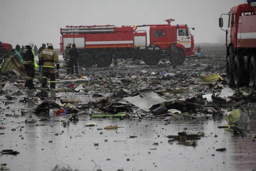 Emergencies Ministry members and investigators work at the crash site of the Flydubai plane crash on March 19, 2016.