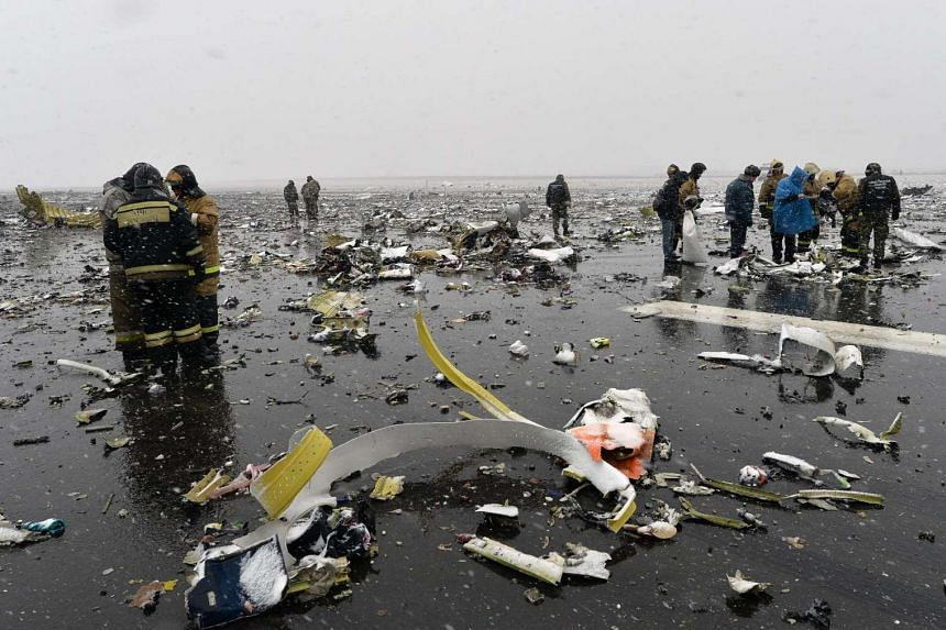 Firefighters search for the flight recorders among debris scattered on the runway after the Flydubai plane crash on March 19, 2016.