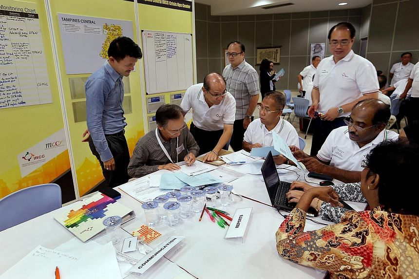 Mr Baey (left) observing the discussion between religious and community leaders during the Inject-Based Exercise at Living Hope Methodist Church yesterday. Mr Steven Lim (third from left), chairman of Tampines Central IRCC, was also present.
