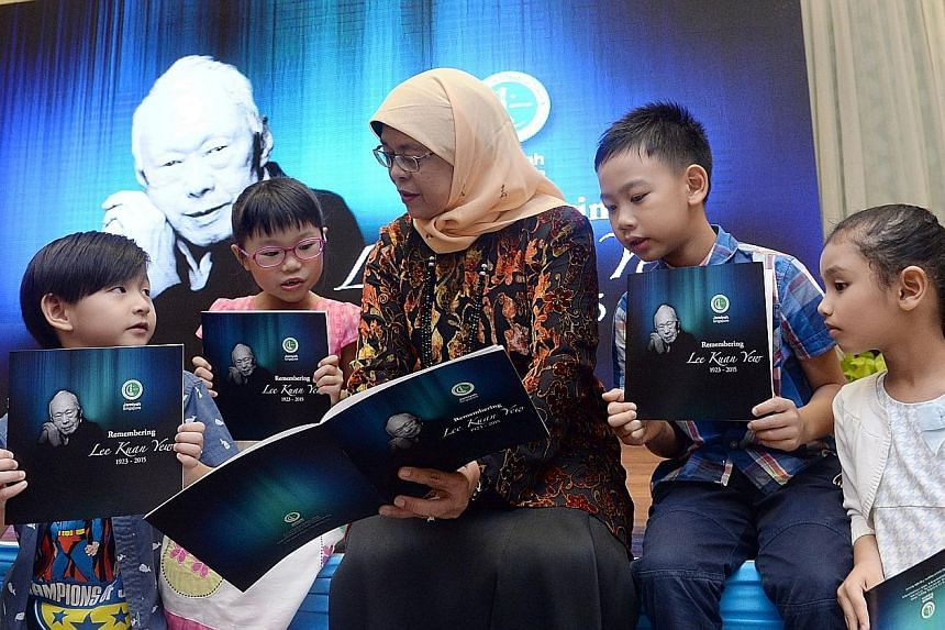 Madam Halimah with kids from the Global Child Development Centre - (from left) Theodore Fun, six, Choo Shaoning, eight, Hong Ee Kent, eight, and Wardah Solehah, six - at Jamiyah's remembrance event for Mr Lee. Workers setting up display panels with p