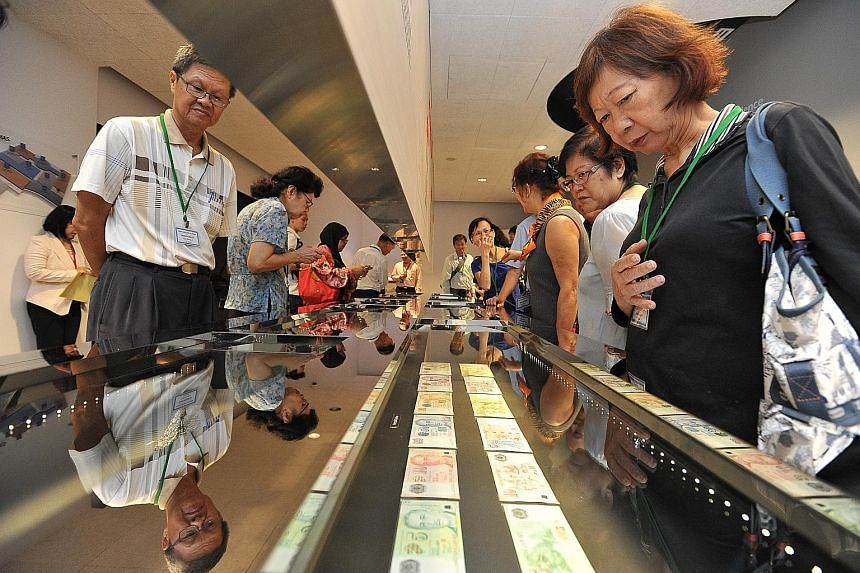 A stronger Singdollar against the greenback is a boon for Singapore tourists. (Above) Visitors viewing the currency notes and coins on display at the MAS Gallery.