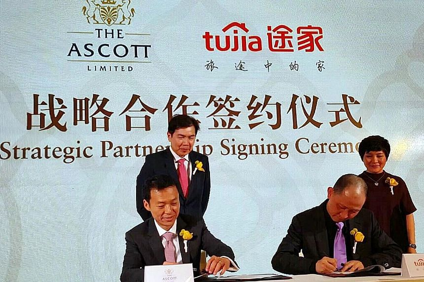 Mr Lim Ming Yan (left), CapitaLand president and group CEO, and Tujia co-founder Melissa Yang looking on as Mr Lee, Ascott CEO (seated left) and Mr Luo, Tujia CEO, signed their joint venture yesterday.