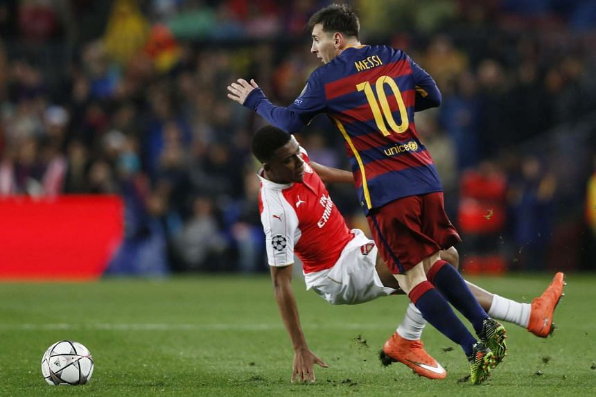 Arsenal's Alex Iwobi in action against Barcelona's Lionel Messi (right).