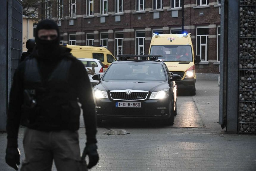 Belgian policemen stand guard while a vehicle and an ambulance leave during the police action.