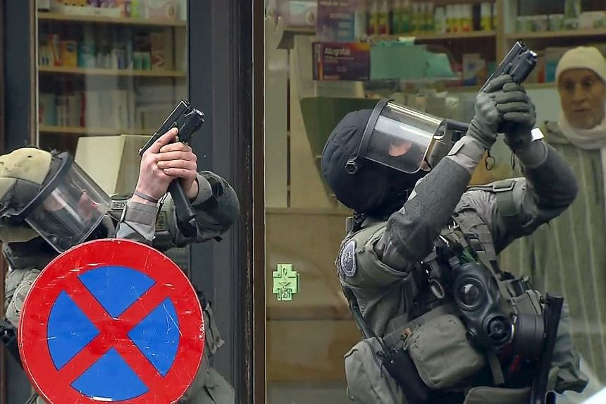 Armed Belgian police secure the area, in this still image taken from video, upon their arrival in Molenbeek.