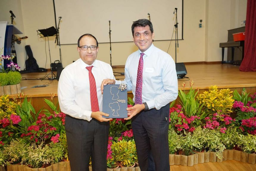 Eurasian Association president Benett Theseira (right) presenting the book Our City, Our Home: Singapore Eurasians 1965-2015 to Mr S Iswaran on March 19, 2016.