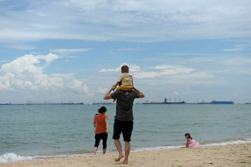 A family spending time at the beach at East Coast Park.