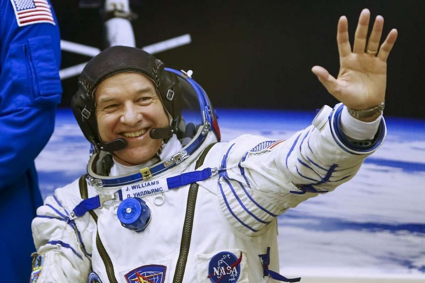 US grandfather Jeff Williams waving after donning a space suit at the Baikonur cosmodrome in Kazakhstan on March 18.