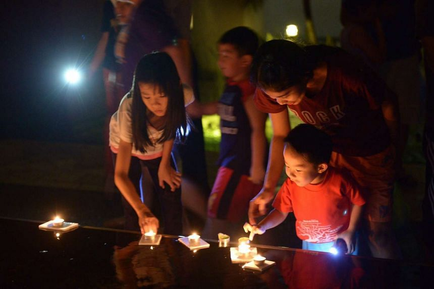 Residents marking Earth Hour by lighting candles at a condominium in Jurong on March 29, 2014.