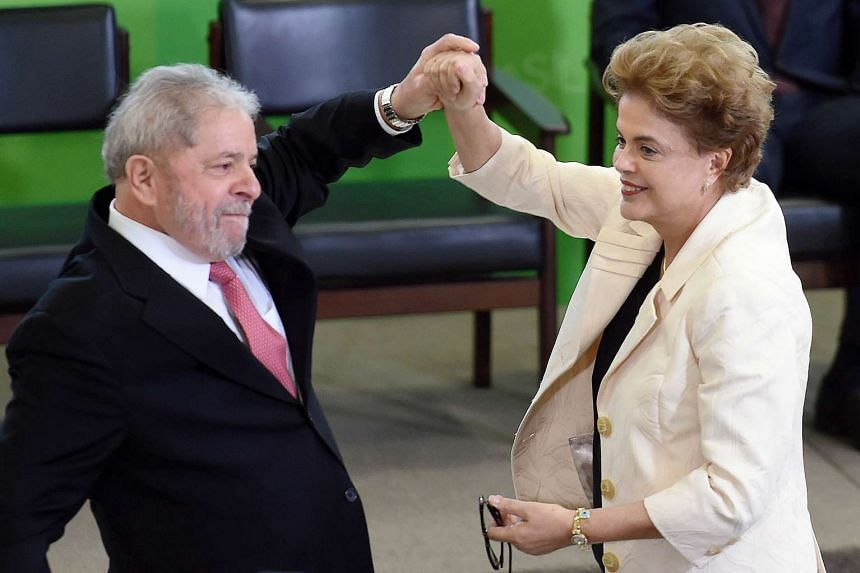 Lula (left) and president Dilma Rousseff gesture during his chief of staff  swearing-in ceremony on March 17, 2016.