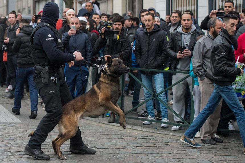 A Belgian police dog handler holds back curious onlookers.