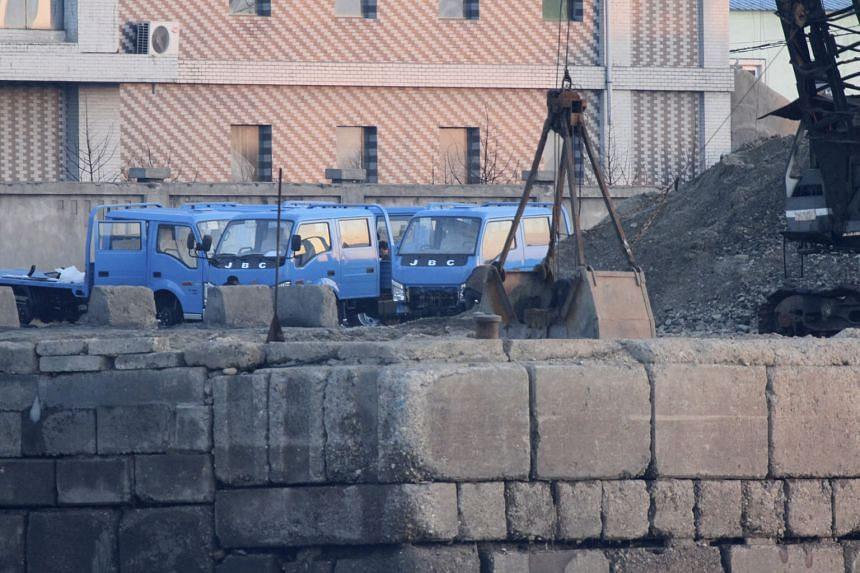 Trucks sit beside a pile of coal on the North Korean side of the Yalu river, opposite the Chinese border city of Dandong, this week. Coal is one of the North's only sources of hard currency and its largest single export item.