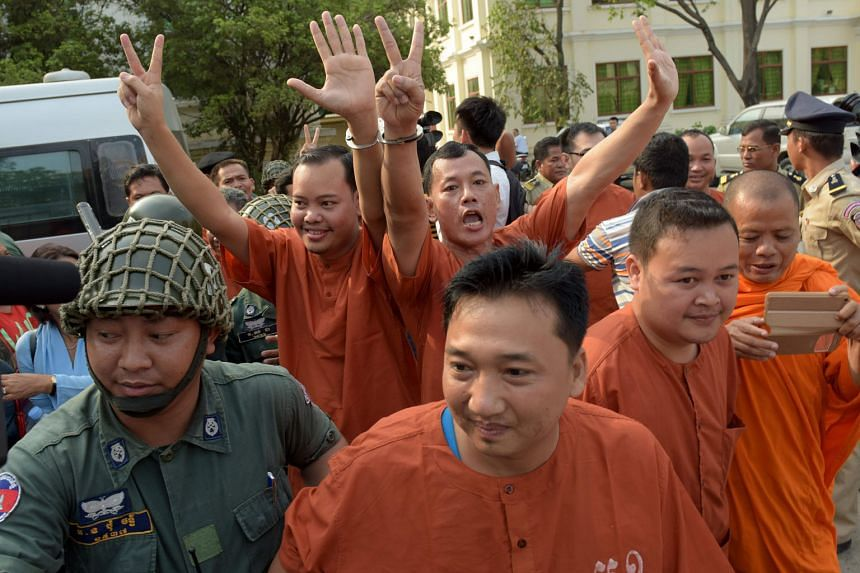 Jailed Cambodian opposition members and activists being escorted by police officials outside the appeal court in Phnom Penh on Thursday.