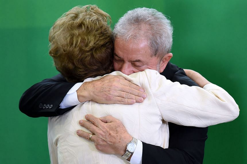 Mr Lula hugging Mrs Rousseff after she swore him into office on Thursday. He has been charged with graft, while she faces being impreached.