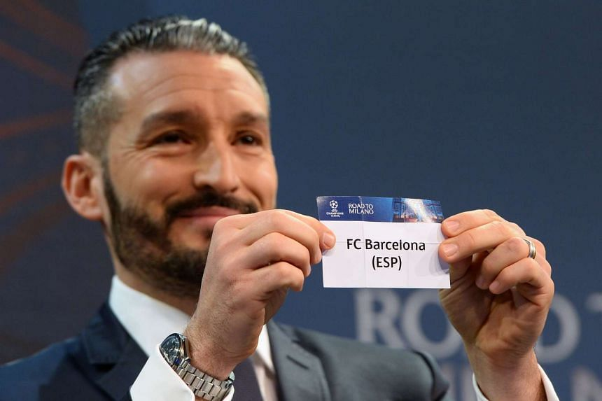 Former Italian footballer Gianluca Zambrotta showing a piece of paper bearing the name of FC Barcelona during the quarter-final draw for the UEFA Champions League on March 18.