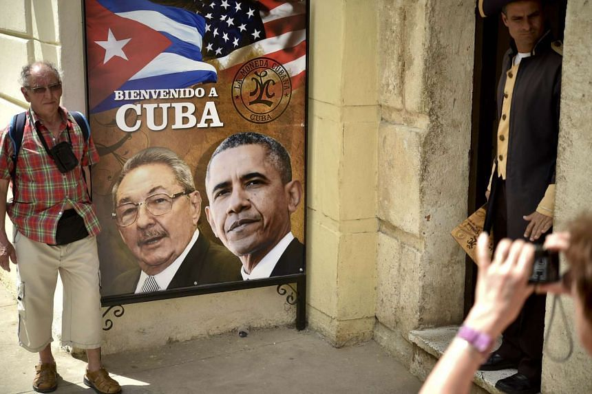 A tourist poses for a picture with a sign placed at the entrance of a restaurant with the images of Cuban and US Presidents Raul Castro and Barack Obama in Havana, Cuba on March 19, 2016.