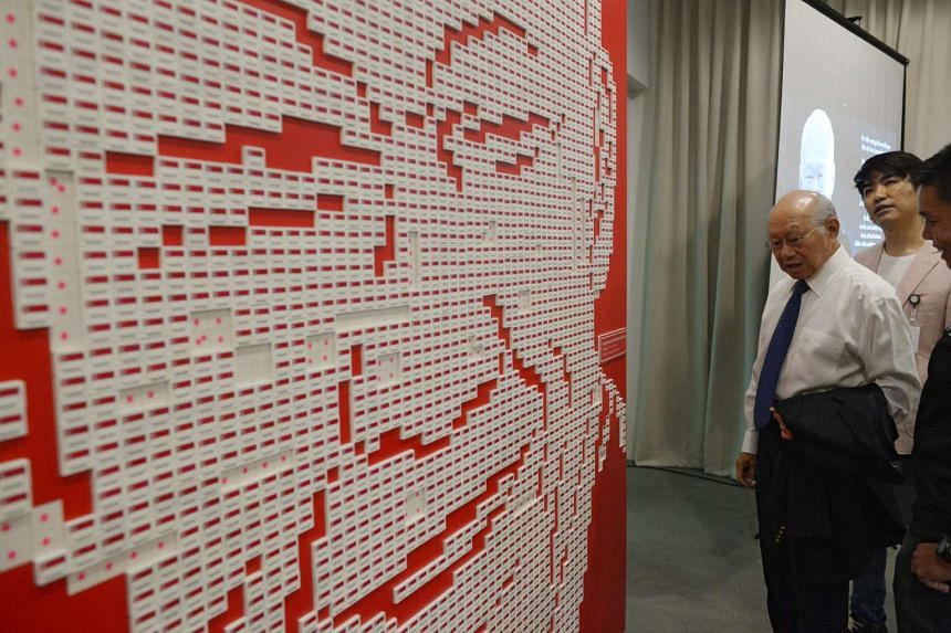 Dr Lee Suan Yew looks at the art installation made up of 4877 Singapore flag erasers featuring the portrait of his brother, the late Mr Lee Kuan Yew, on March 20, 2016.