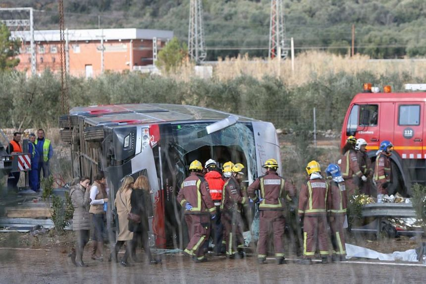 Firemen work at the site of a coach crash that has left at least 14 students dead at the AP-7 motorway in Freginals, northeastern Spain on March 20, 2016.