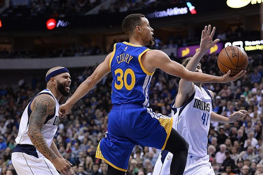 The Warriors' Stephen Curry going to the basket as the Mavs' Dirk Nowitzki tries to block him, with Deron Williams urging him on. Golden State won 130-112 and improved to 62-6.