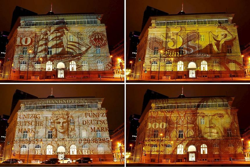 "A branch of Deutsche Bank is illuminated with banknotes of Germany's former currency, the deutsche mark, for the ""Luminale, light and building"" event in Frankfurt."