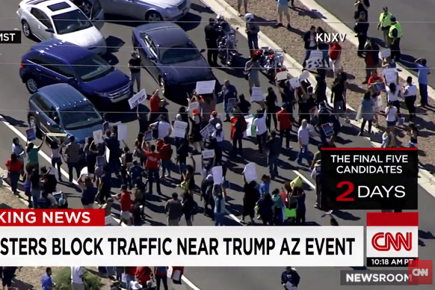 A screenshot from a CNN report shows anti-Trump protesters blocking the highway.