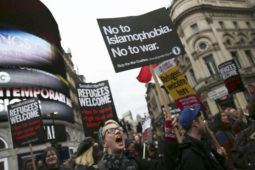 Demonstrators hold placards during a refugees welcome march in London, Britain March 19, 2016.